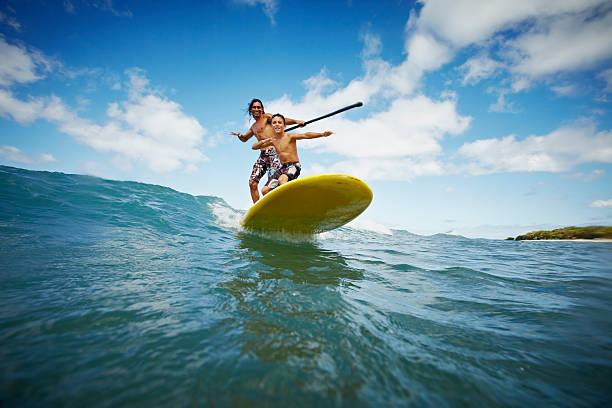 Father and son riding wave on stand up paddleboard