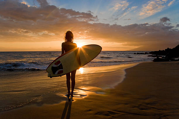 Surfer girl silhouette with surfboard in south Maui, Hawaii, USA.